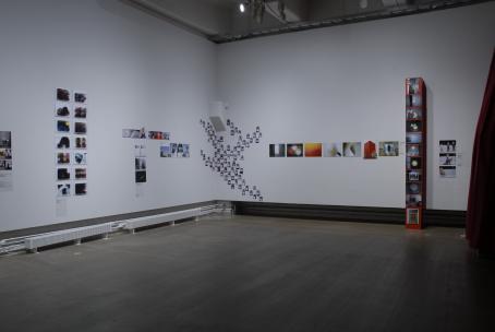 Näyttelytila, jossa on paljon kuvia seinillä.