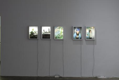 Seinällä on rivissä viisi ohutta laatikkoa, joissa kaikissa on erilainen valaistu valokuva. Laatikoista roikkuu sähköjohdot alas lattialle.