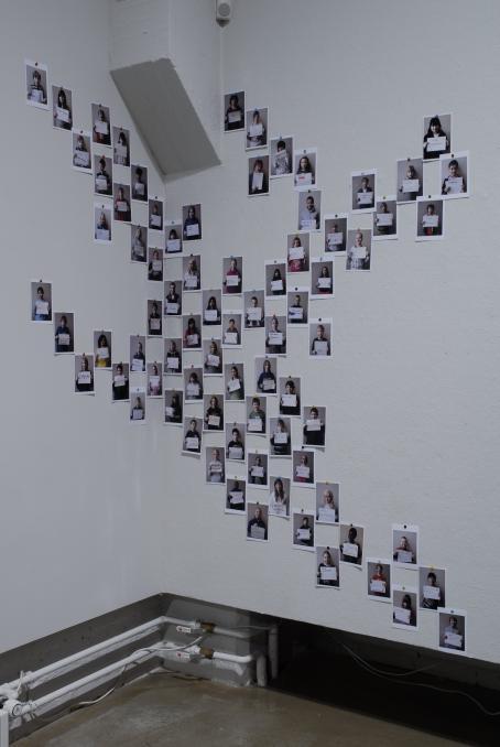 Seinälle epäsäännölliseen muotoon ripustettuja valokuvia. Kaikissa näyttäisi olevan henkilö pitelemässä paperia edessään.