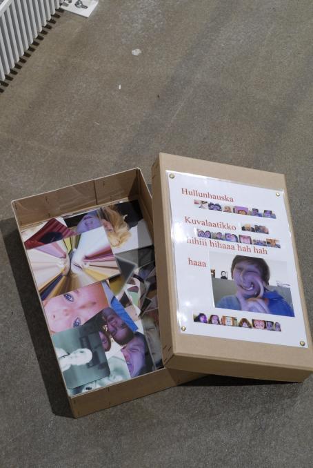 """Matala pahvilaatikko, jonka pohja on peitetty valokuvilla, joissa on ihmisten kasvoja muokattuna erilaisilla filttereillä. Laatikon kannessa lukee """"Hullunhauska Kuvalaatikko hihiii hahaaa hah hah haaa""""."""