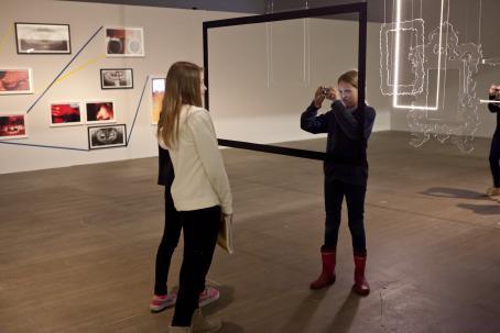 Näyttelytilassa nuori tyttö ottaa kuvaa toisesta tytöstä katosta roikkuvan, ison mustan kehyksen läpi.