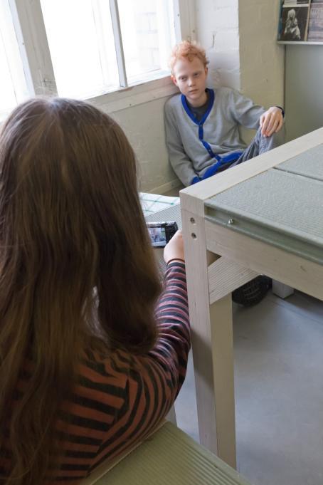 Poika istuu ikkunan edessä olevalla penkillä ja nojaa seinään. Kuvan vasemmassa laidassa tyttö ottaa kuvaa hänestä.
