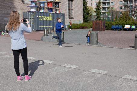 Sinipaitainen poika juoksee jalkakäytävällä. Molemmin puolin jalkakäytävää on tyttö ottamassa hänestä kuvaa. Toinen seisoo, toinen on kyykyssä.