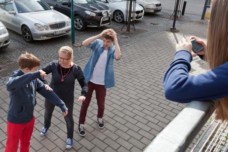 Kolme henkilöä seisoo jalkakäytävällä. Yksi on nostanut kätensä nyrkissä ylös. Hänen edessään seisoo henkilö kädet hieman ylhäällä kuin estämässä. Hänen takanaan on henkilö joka on nostanut kätensä pään päälle. Oikeassa reunassa ylempänä on henkilö ottamassa kuvaa tilanteesta.