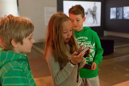 Nuori tyttö katsoo kamerasta kuvia. Hänen vieressään seisoo kaksi nuorta poikaa.