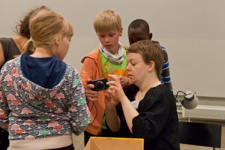 Nuori poika näyttää kamerasta kuvia aikuiselle. Heidän ympärillään on kaksi muutakin lasta.