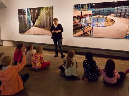 Lapsia istuu lattialla, yksi on nostanut kätensä ylös. Heidän edessään seisoo aikuinen, jonka takana seinällä on valokuvateoksia.