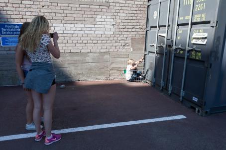 Lapsi istuu seinän vieressä olevan kontin edessä lähellä seinää, hän pitää edessään matalaa metalliaitaa.