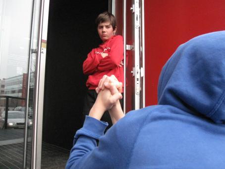 Punapaitainen nuori seisoo oviaukossa kädet ristissä rinnalla ja näyttää vakavalta. Selin kameraan on maassa ehkä polvillaan oleva hahmo, jolla on sininen huppari ja huppu päässä. Hän pitää ristissä olevia käsiään koholla.