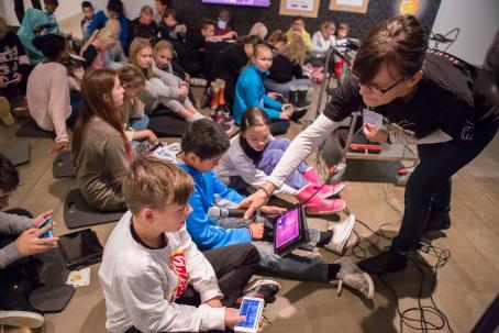 Lattialla istuu lapsia joilla kaikilla on puhelin tai tabletti kädessä. Etualalla on nainen, joka on kumartunut ojentamaan mikrofonin yhdelle lapselle, joka ilmeisesti puhuu siihen.