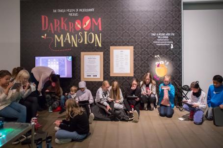 Lattialla istuu lapsia, lähes kaikilla on kädessä puhelin tai tabletti jolla he pelaavat. Takana seinällä on tumma tapetti ja siinä lukee Darkroom Mansion.