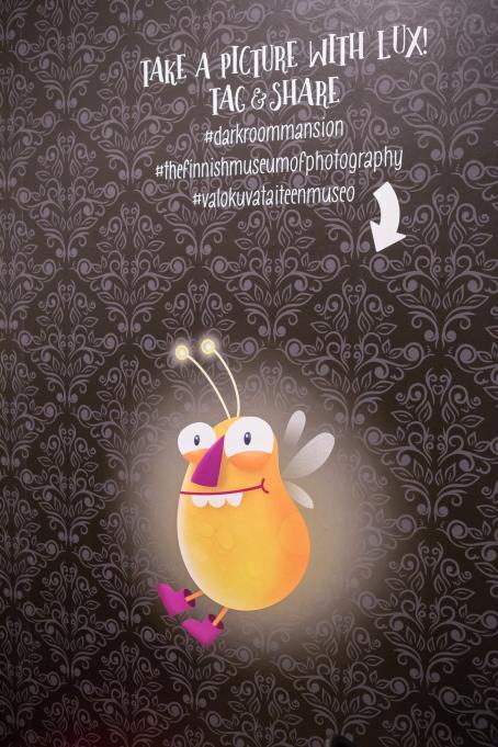 """Tummalla tapetilla peitetyllä seinällä on kuva oranssista, hohtavasta ötökästä ja yläpuolella teksti: """"Take a picture with Lux! Tag and share #darkroommansion """"thefinnishmuseumofphotography #valokuvataiteen museo""""."""