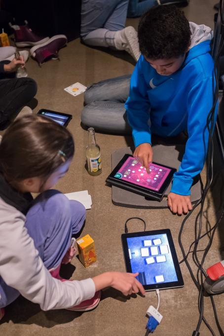 Kaksi lasta istuu lattialla tabletit edessään. He pelaavat Darkroom Mansion-peliä.