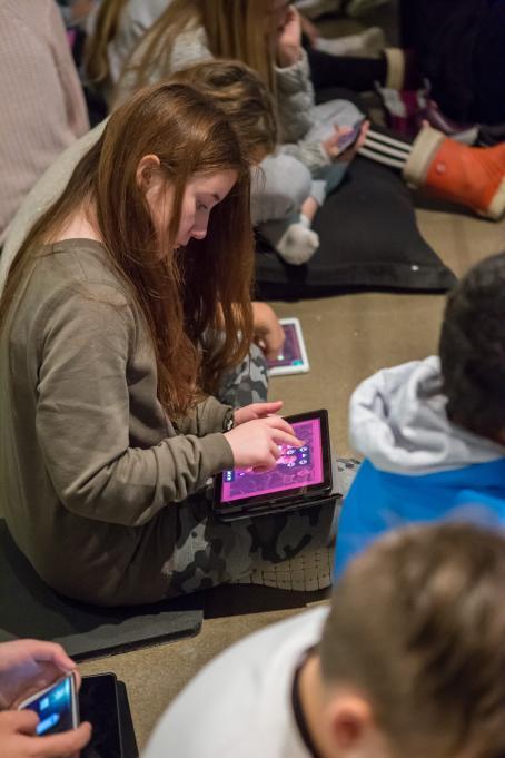 Lapsi istuu lattialla tabletti kädessään ja pelaa Darkroom Mansion-peliä. Hänen ympärillään istuu paljon muitakin lapsia.
