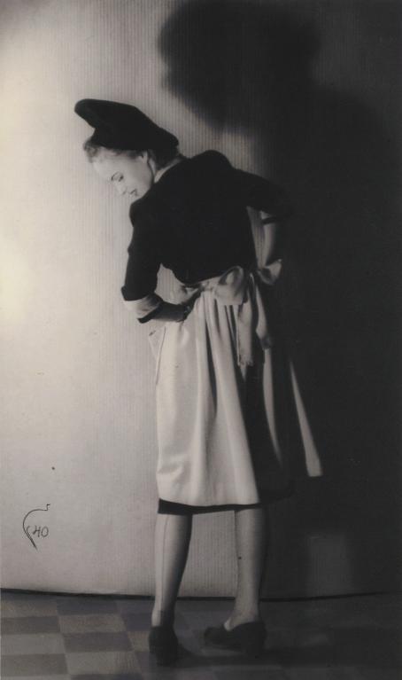 Mustavalkoisessa kuvassa nainen seisoo selin kameraan ja katsoo taakse alas jalkoihinsa niin, että hänen kasvonsa näkyvät. Kädet ovat lanteilla. Naisella on päällään tumma baskeri, tumma paita ja vaalea hame. Hänen varjonsa lankeaa tummana ja suurena takana olevalle seinälle.