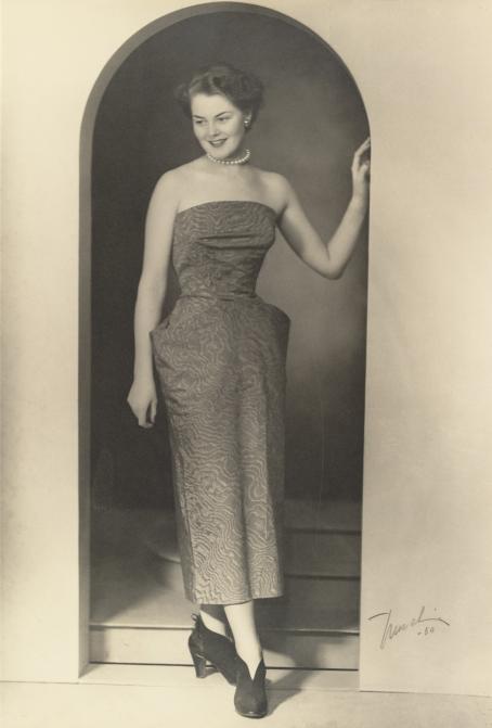 Mustavalkoisessa kuvassa nainen seisoo kaarevassa oviaukossa. Hänellä on päällään olkaimeton iltapuku, jossa on lantion kohdalla terävät levennykset. Hän hymyilee. Toinen käsi nojaa oviaukkoon.