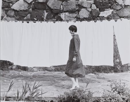 Mustavalkoisessa kuvassa lyhythiuksinen nainen raidallisessa mekossa kävelee pyykkinarulla roikkuvien lakanoiden edessä.