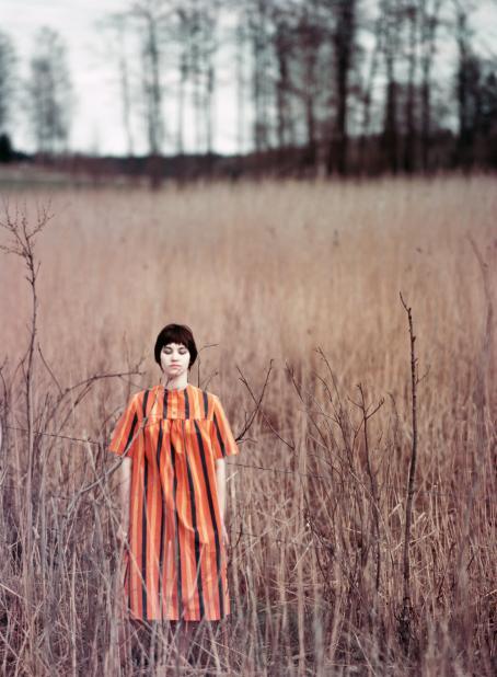 Lyhythiuksinen nainen oranssissa pystyraitaisessa mekossa seisoo niityllä tai pellolla. Naisella on silmät kiinni. Hänen ympärillään kasvaa vaaleanruskeaa heinää.