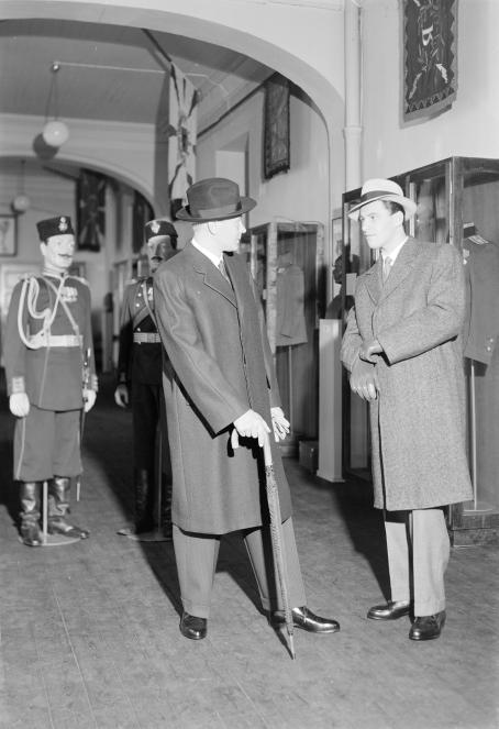 Mustavalkoisessa kuvassa kaksi miestä pitkissä takeissa, suorissa housuissa ja hatut päässä seisoo kuin keskustellen. Toisella on sateenvarjo kädessä. Miesten takana on käytävä, jonka keskellä on kaksi univormupukuista, viiksekästä patsasta. Miehet on valaistu voimakkaasti edestäpäin ja heistä lankeaa pitkät varjot.