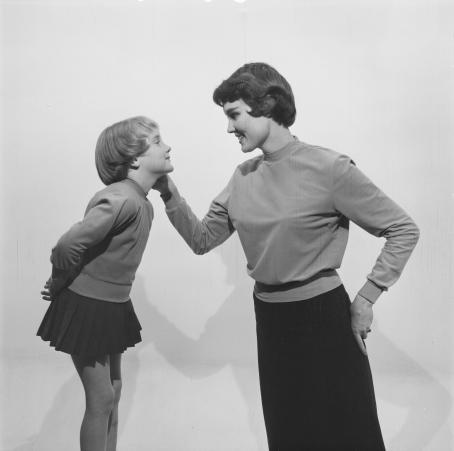 Mustavalkoisessa kuvassa nainen ja lapsi katsovat toisiaan. Nainen pitää kättään lapsen poskella. Lapsi on naisen kanssa lähes samalla tasolla. Molemmilla on päällään yksinkertaiset pitkähihaiset paidat ja tummat hameet. Lapsen hame on todella lyhyt, naisen taas pitkä.