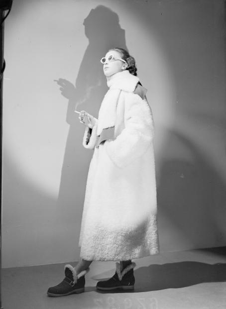 Mustavalkoisessa kuvassa nainen vaaleassa, pehmeässä, ehkä turkistakissa, seisoo pidellen toisessa kädessään savuavaa savuketta. Toinen käsi on taskussa. Hänellä on aurinkolasit ja hän katsoo yläviistoon. Häneen kohdistuu pyöreä valokeila ja hänestä lankeaa varjo takana olevalle seinälle.