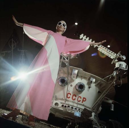 Alaviistosta otettu kuva, jossa etualalla seisoo nainen leveäraitaisessa vaaleanpunavalkoisessa mekossa. Hänellä on suuret aurinkolasit, ja hän on levittänyt kätensä sivuille. Naisen takana on jonkinlainen valkoinen laite, jossa on kirjaimet CCCP. Naisen vierestä takaa tulee myös kirkas valo.