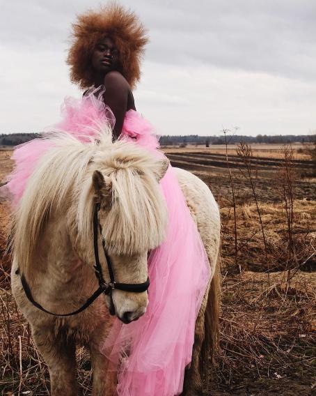 Tummaihoinen nainen istuu pienen hevosen tai ponin selässä. Hänellä on päällään vaaleanpunainen tyllihame tai -mekko, jonka helma roikkuu ponin kylkeä vasten lähes maassa asti. Naisella on vaaleanruskea afrotukka. Takana näkyy kynnettyä peltomaisemaa.