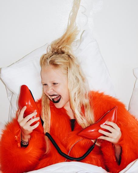 Ylhäältäpäin otettu kuva, jossa vaaleatukkainen nainen makaa sängyllä valkoisissa lakanoissa. Naisella on päällä punainen turkistakki. Hän pitää molemmissa käsissä punaisia huulten muotoisia esineitä, joiden välillä kulkee musta kierteinen johto. Naisen suu on auki kuin hän huutaisi.