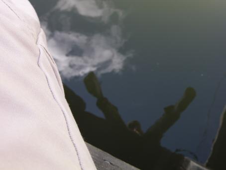 Kuvan vasemmassa reunassa näkyy vähän ihmisen jalkaa. Alhaalla näkyy vettä, josta heijastuu ihmisen jalat.