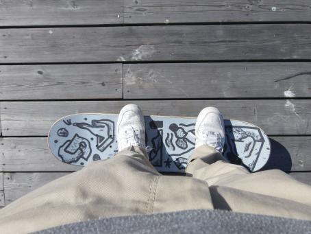 Henkilö seisoo skeittilaudan päällä. Hänellä on vaaleanruskeat housut ja valkoiset tennarit. Skeittilautaan on piirretty mustalla kuvioita. Kuva on otettu ylhäältä päin, noin henkilön vatsan kohdalta.