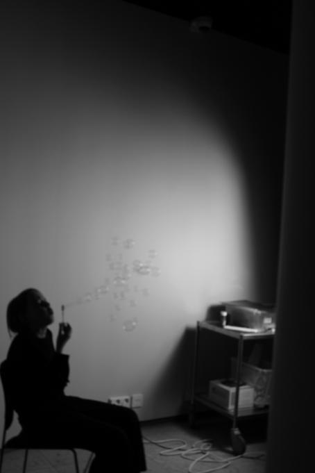 Mustavalkoisessa kuvassa nuori henkilö istuu tuolilla ja puhaltaa saippuakuplia. Kuva on tumma, henkilön taakse seinälle tulee valoa mutta muuten kuva on varjoisa.