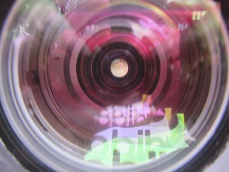 Pyöreä esine, jonka päällä on läpinäkyvä lasi. Sisällä on ikäänkuin putki, joka kapenee tasoittain, ja sen keskellä on pieni reikä. Lasista heijastuu Adidaksen logo.