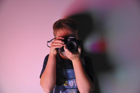 Henkilö seisoo vasten vaaleanpunaisena hohtavaa seinää. Hän pitää kasvojensa edessä järjestelmäkameraa.
