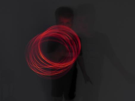Hämärässä kuvassa on henkilö ja hänen edessään valoympyrä. Kuva on otettu pitkällä valotusajalla ja henkilö on pyörittänyt valonlähdettä ympyrän muodossa.