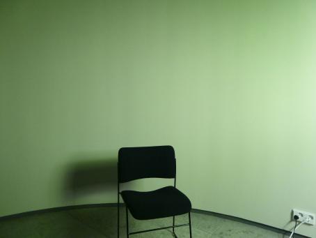 Huoneessa yksi musta tuoli, josta lankeaa varjo seinälle. Seinä on vihreän sävyinen. Seinässä on myös pistorasia, johon on kiinnitettynä kaksi johtoa.