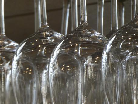 Viinilaseja ylösalaisin vieri vieressä. Niistä on rajautunut pois ylimmät osat ja alimmat osat.