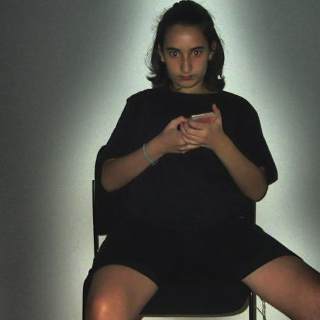 Mustalla tuolilla istuu henkilö mustassa t-paidassa ja mustissa shortseissa. Hän pitää puhelinta molemmin käsin. Hänen silmissään on punaiset pisteet. Hänen ympärillään on vaalea valokehä.