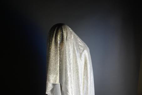 Hahmo, jonka päällä on valkoinen kangas, jossa on kimaltelevia kultaisia paljetteja. Tausta on tasaisen tummanharmaa.