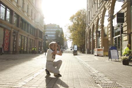 Nuori henkilö ottamassa kuvaa keskellä kaupungin katua. Hän on kyykyssä ja on tähdännyt kameransa yläviistoon. Kadun varrella olevissa rakennuksissa on esim. Marimekko ja Picnic.
