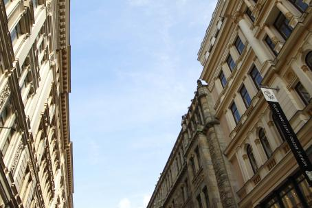 Kahden vanhan ja koristeellisen rakennuksen välistä näkyy sinistä taivasta, jossa on ohutta valkoista pilveä.