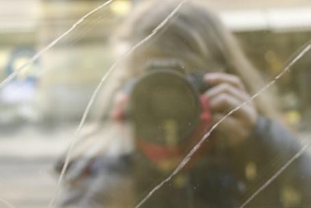 Kuvaaja näkyy heijastavasta pinnasta, jonka halki kulkee viivoja, säröjä, samaan suuntaan. Kamera peittää kuvaajan kasvot kokonaan.