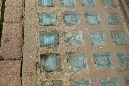 Maassa betoniin upotettuna vaaleansinisen sävyisiä neliöitä riveissä. Osa neliöistä on rikkoutunut ja lohjennut.