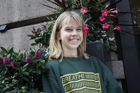Hymyilevä nuori tyttö seisoo kukkaistutusten edessä. Hänellä on vihreä paita, jossa lukee Breathe.