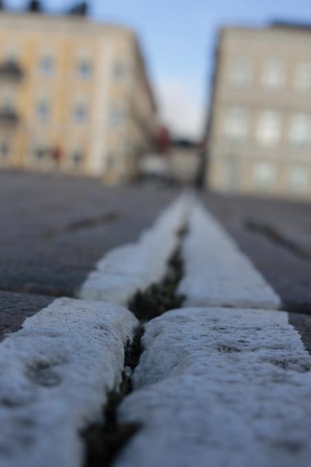 Maantasosta otettu kuva, jonka keskellä on tiessä oleva valkoinen viiva. Taaempana näkyy rakennuksia. Ainoastaan pieni alue etualalla on tarkkaa.