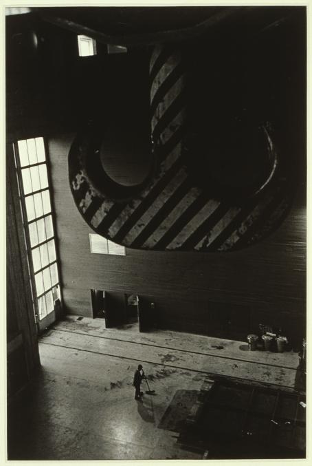 Mustavalkoisen kuvan yläosassa on ilmeisesti katosta riippuva, massiivinen raidallinen ankkurin mallinen koukku tms. Kaukana alhaalla minimaaliselta vaikuttava mies harjaa hallin lattiaa.