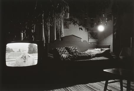 """Mustavalkoisessa kuvassa mies makaa puisella sivustavedettävällä sohvasägyllä. Sängyn yläpuolella oleva lamppu valaisee huoneen. Sängyn vieressä on televisio, jonka ruudulla on mies ja teksti """"Aarne Tanninen, Washington""""."""