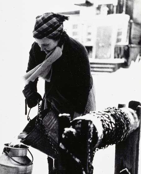 Mustavalkoisessa kuvassa huivipäinen nainen kaataa kaivosta nostamansa veden ämpäristä maitotonkkaan. Kaivon yläosa näkyy kuvassa.