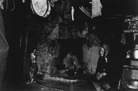 Mustavalkoisessa, tummasävyisessä kuvassa massiivisen ja likaisen tulisijan vieressä istuu vanha nainen tummissa vaatteissa. Ylempänä takan reunalla istuu kissa, josta erottuu lähinnä vain kiiluvat silmät. Kuvan yläreunassa näkyy osittain katosta roikkuvia vaatteita.