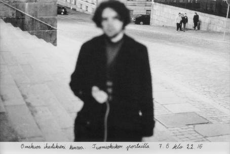 """Mustavalkoisessa kuvassa etualalla on epäterävä miehen hahmo, joka seisoo leveillä portailla. Miehen takana on alaspäin viettävä katu, jonka reunassa kävelee ihmisiä. Heistä yhden pää on ympyröity. Kuvan alareunaan on käsin kirjoitettu: """"Omakuva ihastukseni kanssa. Tuomiokirkon portailla 7.5. klo 22:15."""""""