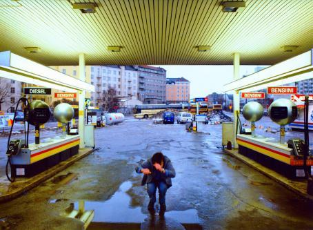 Näkymä huoltoasemalta kahden tankkauspisteen välistä. Harmaatakkinen mies on kyykyssä vesilätäkön edessä, kädet liike-epäterävinä edessä kuin hän olisi juuri hyppäämässä.